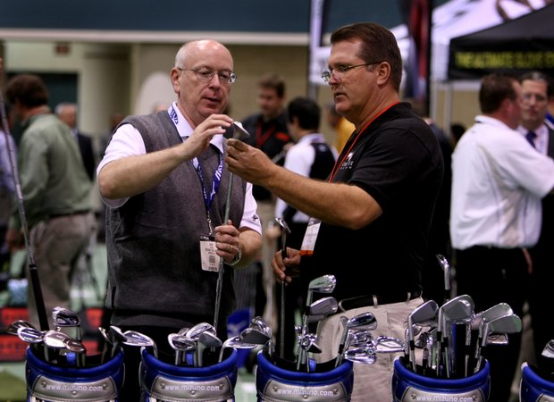 Gary Pierce (left), a player promotion manager, and Rocky Kinsey, golf professional at Eastwood Golf Club in Orlando, Fla., look at Mizuno wedges at the PGA Merchandise Show's indoor range.