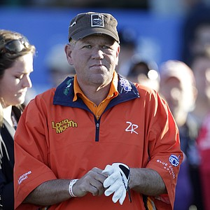 John Daly pulls on his glove as he surveys the first fairway while waiting to start the first round of the Farmers Insurance Open golf tournament in San Diego, Thursday, Jan. 27, 2011.