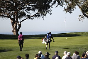 Tiger Woods and caddie Steve Williams approach the ocean front 12th green on the North Course at Torrey Pines where Woods' tee rest inches from the hole during the first round of the Farmers Insurance Open golf tournament in San Diego, Thursday, Jan. 27, 2011
