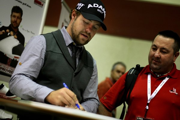 The crowd at the True Linkswear booth Friday snapped pictures of Ryan Moore as he autographed posters.