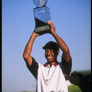 Tiger Woods holds his trophy aloft after winning the Las Vegas Invitational in Las Vegas, Nevada. It was the first win of his pro career.