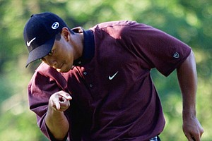 In this Aug. 20, 2000 photo, Tiger Woods points to his ball as it drops for birdie on the first hole of a three-hole playoff against Bob May at the PGA Championship at Valhalla Golf Club in Louisville, Ky. (AP Photo/Chuck Burton, File)