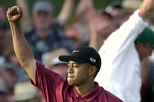 "Tiger Woods reacts on the 18th hole after winning the 2001 Masters by two strokes over David Duval at the Augusta National Golf Club in Augusta, Ga. The win was Woods' fourth straight major title, completing what many would call the ""Tiger Slam."""