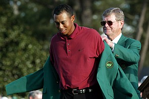 "Tiger Woods, left, receives the 2002 Masters Green Jacket from Augusta National Golf Club chairman William W. ""Hootie"" Johnson. The win was Woods' third Masters title and second in a row."