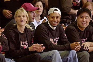 Tiger Woods, center, sits with his fiancee Elin Nordegren, left, and his friend Jerry Chang, right, during Stanford's basketball game against Arizona in this Feb. 7, 2004.