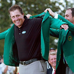 Phil Mickelson accepts his green jacket from 2003 winner Mike Weir.