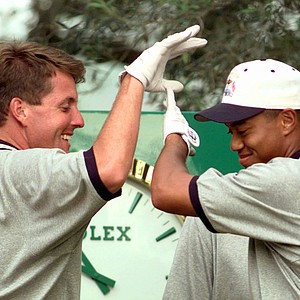 Phil Mickelson and Tiger Woods high-five during practice for the 1997 Ryder Cup at Valderrama Golf Course in Spain.