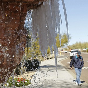 A spectator walks toward the TPC Scottsdale as icicles form on a water fountain at the Sheraton Desert Oasis Resort in Scottsdale, Ariz., Wednesday, Feb. 2, 2011.