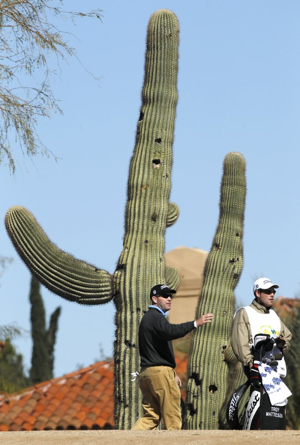 Troy Matteson, left, and his caddie, Patrick Sherry, are dwarfed by a saguaro cactus as Matteson prepares to hit out of the desert at the second hole during the first round of the Phoenix Open PGA golf tournament Thursday, Feb. 3, 2011, in Scottsdale, Ariz.