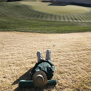 With frost around the 18th green, volunteer Richard Carlson, of Sun City West, Ariz., takes a nap during a frost delay prior to the first round of the Waste Management Phoenix Open.