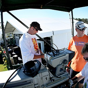 Golf Channel employees (from left) Ryan Swonk, G. Mark Bowden and Jim Wachter set up a camera at No. 18 on the Magnolia course before the 2010 Children's Miracle Network Classic.