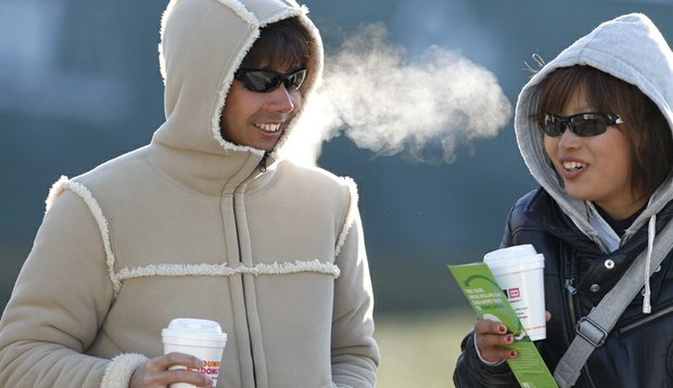 Golf fans try to stay warm as they arrive for the frost delayed first round of the Waste Management Phoenix Open Thursday, Feb. 3, 2011, in Scottsdale, Ariz.