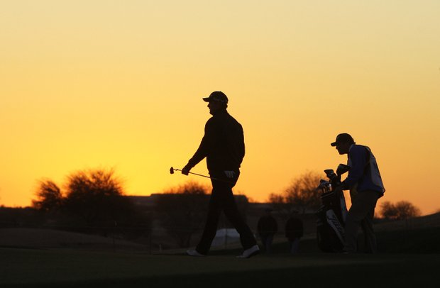 Marc Leishman, left, and caddie Bucky Coe exit the course Friday after the horn sounded to halt play for darkness.