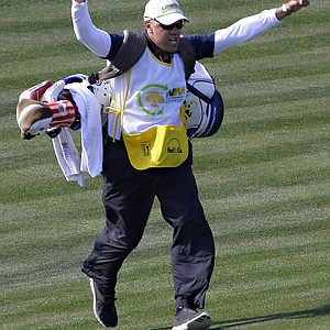 "Jerry Kelly's caddy, Eric Meller runs the length of the fairway onto the 16th green after being prompted by fans during the first round of the Phoenix Open. The tournament's notoriously rambunctious 162-yard, Par-3 16th green, dubbed the ""Rowdiest Hole in Golf"", is completely engulfed by skyboxes and bleachers that can hold up to 20,000 fans."