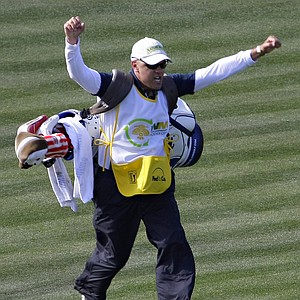 """Jerry Kelly's caddy, Eric Meller runs the length of the fairway onto the 16th green after being prompted by fans during the first round of the Phoenix Open. The tournament's notoriously rambunctious 162-yard, Par-3 16th green, dubbed the """"Rowdiest Hole in Golf"""", is completely engulfed by skyboxes and bleachers that can hold up to 20,000 fans."""