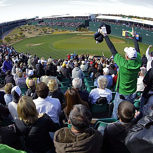 "Fans cheer on the 16th green during the first round of the Phoenix Open. The tournament's notoriously rambunctious 162-yard, Par-3 16th green, dubbed the ""Rowdiest Hole in Golf"", is completely engulfed by skyboxes and bleachers that can hold up to 20,000 fans."