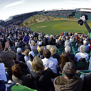 """Fans cheer on the 16th green during the first round of the Phoenix Open. The tournament's notoriously rambunctious 162-yard, Par-3 16th green, dubbed the """"Rowdiest Hole in Golf"""", is completely engulfed by skyboxes and bleachers that can hold up to 20,000 fans."""