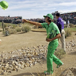 Rickie Fowler throws hats to the fans on the 16th green during the second round of the Phoenix Open Saturday, Feb. 5, 2011, in Scottsdale, Ariz.