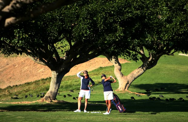 Head coach Laurie Gibbs, left, talks with freshman Grace Na as she hits balls at the practice area.