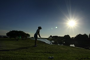 Taylore Karle is silhouetted by the setting sun as she hits balls toward the Pacific Ocean.
