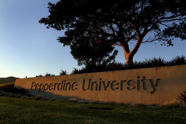 The setting sun lights up the sign at the main entrance to the Pepperdine campus, located among ridges that overlook the Pacific Ocean and the Pacific Coast Highway in Malibu, Calif.