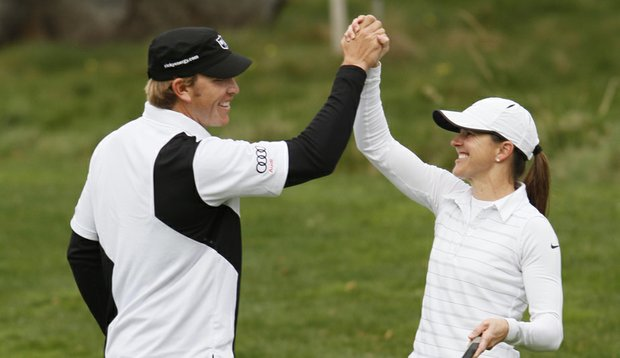 Ricky Barnes high-fives former soccer player Brandi Chastain during the 2010 AT&T Pebble Beach National Pro-Am.