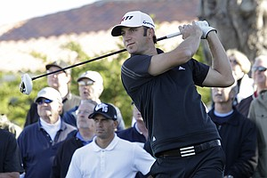 Two-time defending champion Dustin Johnson follows his drive from the first tee of the Monterey Peninsula Country Club as surfer Kelly Slater looks on during the first round of the AT&T Pebble Beach National Pro-Am in Pebble Beach, Calif., Thursday, Feb. 10, 2011.