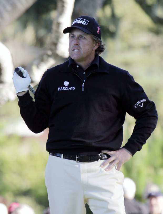 Phil Mickelson reacts after his shot from the third tee of the Monterey Peninsula Country Club during the first round of the AT&T Pebble Beach National Pro-Am in Pebble Beach, Calif., Thursday, Feb. 10, 2011.