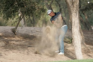 Henrik Stenson wraps his second shot around a tree during the first round in Dubai.