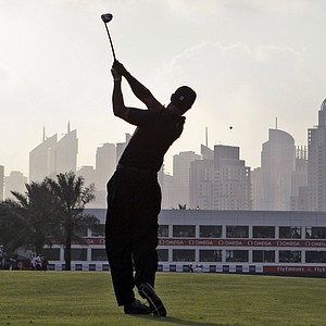 Tiger Woods plays his second shot into the par-5 finishing hole in Dubai. Woods went on to make eagle and shoot 71 in the opening round.