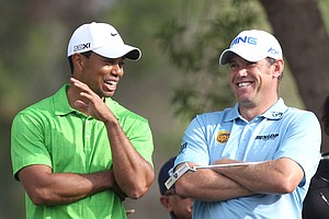 Tiger Woods (L) talks to world number one Lee Westwood of England on the second day of the Dubai Desert Classic golf tournament in the Gulf emirate on February 11, 2011. Woods struggled the previous day coming third best after Westwood and Martin Kaymer in a rare showdown opposing the world's top three golfers.
