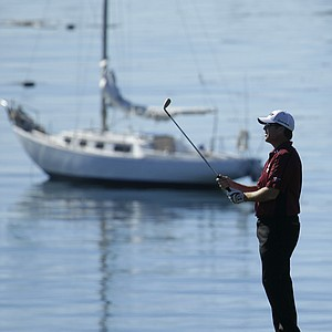 D.A. Points lines up a shot on a picture-perfect day at Pebble Beach.