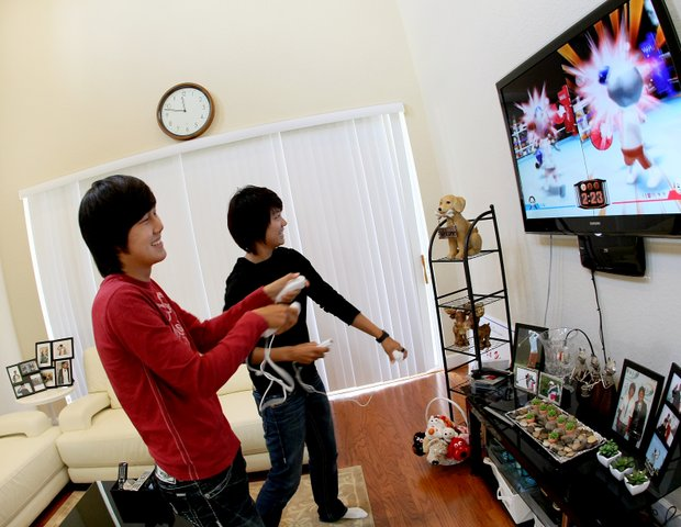 Song Hee Kim, left, and Na Yeon Choi, right, play Nintendo Wii at Choi's home recently.