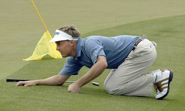 AUGUSTA, : Stuart Appleby of Australia gets down on his hands and knees to line up his putt on the second hole, 11 April 2002, during the opening round for the 2002 Masters Tournament at the Augusta National Golf Club in Augusta, GA.