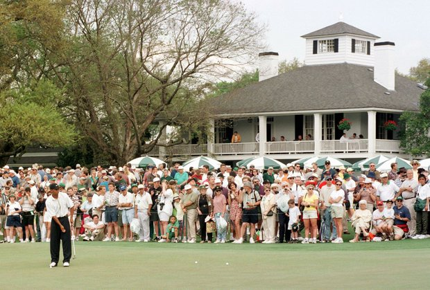 AUGUSTA, : Defending champion Tiger Woods (L) of the US putts on the practice green in front of the clubhouse and a large crowd 08 April at Augusta National Golf Course in Augusta, GA. The four day Masters golf tournament begins 09 April.