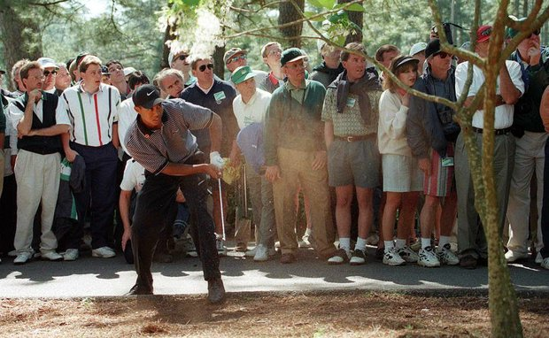 AUGUSTA, : Tiger Woods watches his second shot out of the trees on the 7th hole 10 April during the first round of the Masters golf tournament at the Augusta National Golf Club in Augusta, Georgia. Woods is playing in his first Masters as a professional.