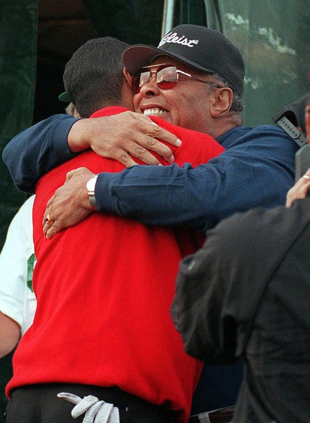 AUGUSTA, : Tiger Woods (L) is hugged by his father Earl Woods near the 18th hole 13 April after winning the Masters tournament at Augusta National Golf Club in Georgia. Woods set a new 72-hole course record by shooting an 18-under-par 270.