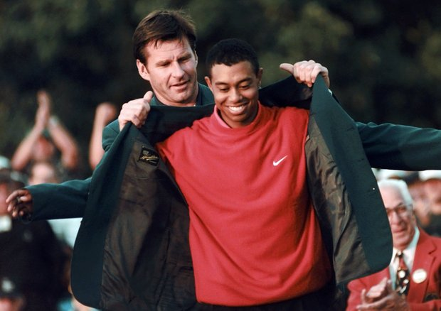 Masters champion Tiger Woods receives his green jacket from the previous year's winner Nick Faldo, rear, at the Augusta National Golf Club in Augusta, Ga.