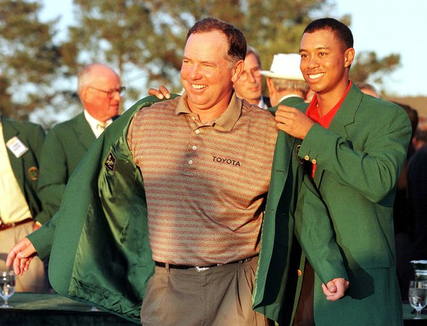 AUGUSTA, : Mark O'Meara (L) gets the Green Jacket from Tiger Woods, the defending Masters champion, 12 April at Augusta National Golf Course in Augusta, GA. O'Meara finished at nine-under-par.