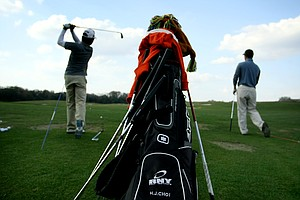 Ho Joon Choi, left, and Nam Kyu Ha, right, work on their swings on the driving range. The Korean students all stay in condos at Reunion Resort.