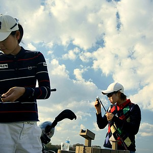 Ji Min An, right, and Jung Min Lee, left, clean their irons after a day of practice. Jung Min Lee won last year on the KLPGA.