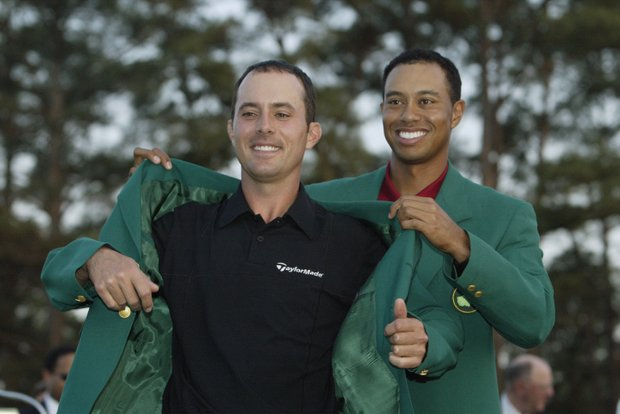 Mike Weir of Canada is presented with the green jacket by Tiger Woods of the USA after winning the play off after the final round of the 2003 Masters Tournament at the Augusta National Golf Club in Augusta, Georgia on April 13, 2003.