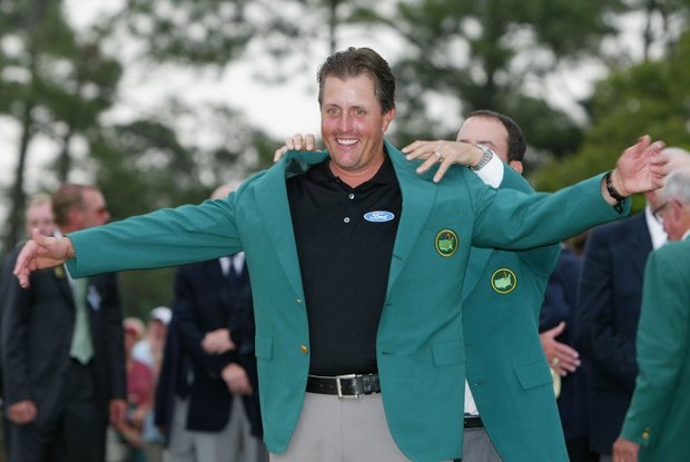 Phil Mickelson of the USA is presented the green jacket by 2003 Masters champion Mike Weir of Canada after the final round of the Masters at the Augusta National Golf Club on April 11, 2004 in Augusta, Georgia.