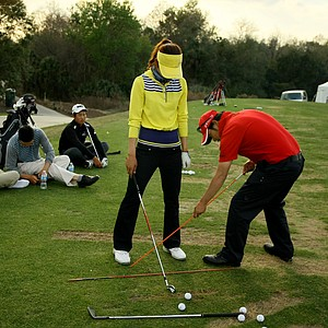 Young J. Kim, right, of RNY Golf Institute works with Hyun Hee Moon on the driving range.