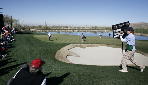 A standard bearer runs around a sand trap on the third green to catch up with Steve Stricker and Matteo Manassero during the first round of the Accenture Match Play Championship.