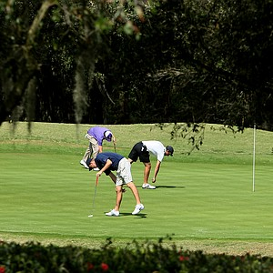 Players in the Golfweek Spring Invitational repair ball marks at No. 2 during the first round.