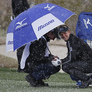 Luke Donald of England, right, ducks under an umbrella with his caddie as snow falls on the 4th fairway while playing Martin Kaymer of Germany in the finals of the Match Play Championship golf tournament Sunday, Feb. 27, 2011, in Marana, Ariz.