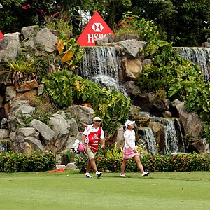 Karrie Webb of Australia hits her second shot on the 18th hole as Chie Arimura of Japan and her caddie look on during the final round of the HSBC Women's Champions at the Tanah Merah Country Club on February 27, 2011 in Singapore.