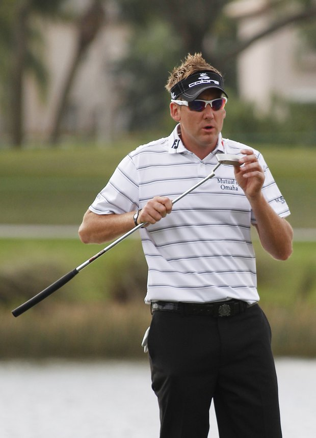 Ian Poulter examines his club before putting on the first hole during the third round of the Honda Classic.