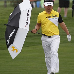 Y.E. Yang uses an umbrella against a light rain as he walks towards his ball on the ninth hole during the third round of the Honda Classic.